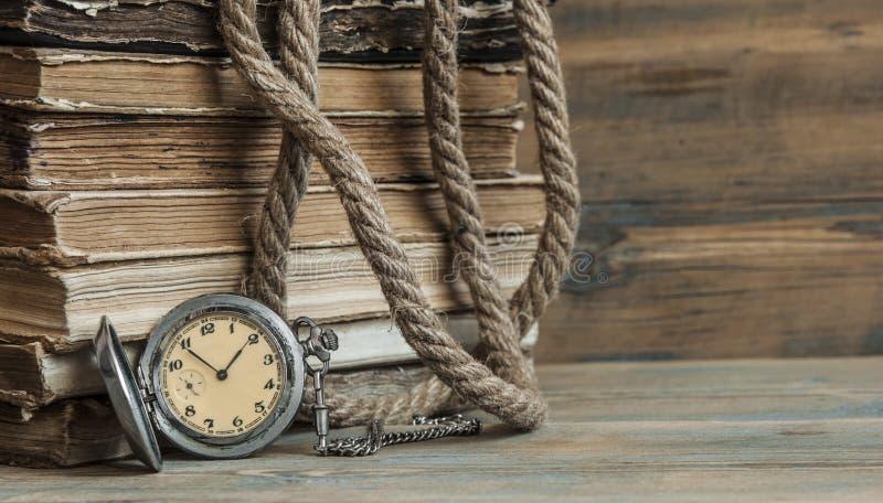 Παλαιά βιβλία με το ρολόι τσεπών σε έναν ξύλινο πίνακα στοκ εικόνες