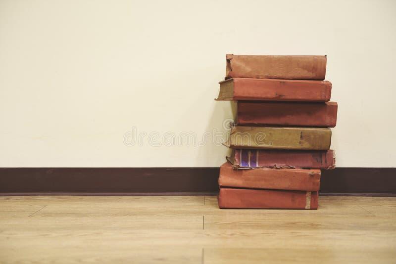 Παλαιά βιβλία σε ένα ξύλινο πάτωμα - κρατήστε το σωρό στο δωμάτιο βιβλιοθηκών για το υπόβαθρο τοίχων επιχειρήσεων και εκπαίδευσης στοκ εικόνα