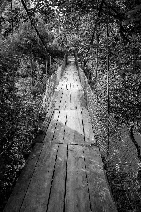 Παλαιά γέφυρα για πεζούς αναστολής που καλύπτεται με τις ξύλινες σανίδες στο χωριό Debnevo, βουνό Stara Planina, Βουλγαρία μαύρο  στοκ φωτογραφία με δικαίωμα ελεύθερης χρήσης
