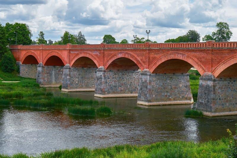 Παλαιά γέφυρα τούβλου πέρα από τον ποταμό Venta στην πόλη Kuldiga, στοκ φωτογραφία με δικαίωμα ελεύθερης χρήσης