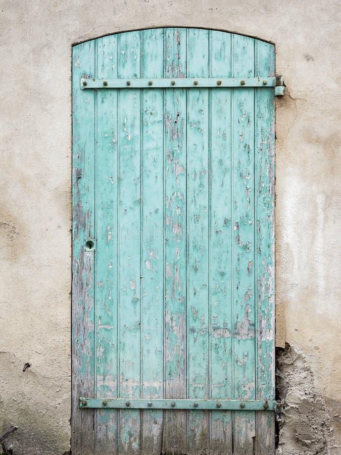 Παλαιά γαλαζοπράσινη πόρτα με το χρώμα αποφλοίωσης στοκ εικόνες