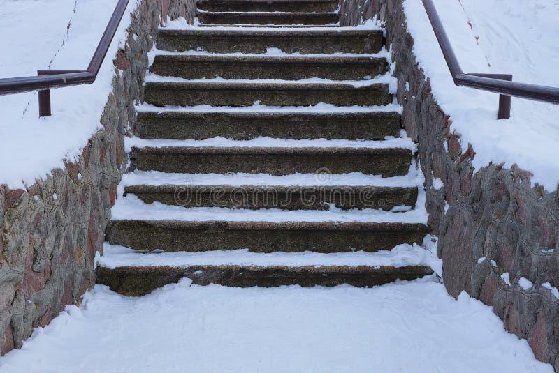 Παλαιά γκρίζα συγκεκριμένη σκάλα με τα βήματα πετρών κάτω από το άσπρο χιόνι στοκ φωτογραφίες