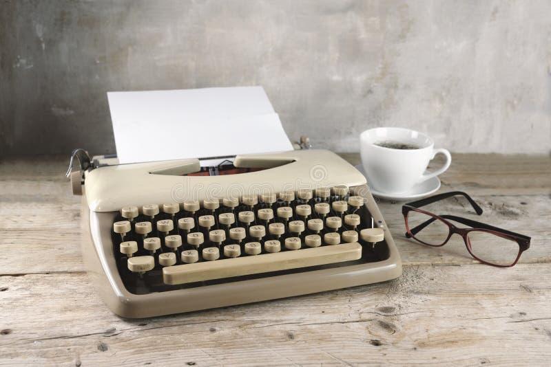 Παλαιά γραφομηχανή από τη δεκαετία του '50 με το κενούς έγγραφο, τον καφέ και τα γυαλιά στο αγροτικό ξύλινο, χλωμό εκλεκτής ποιότ στοκ φωτογραφίες με δικαίωμα ελεύθερης χρήσης