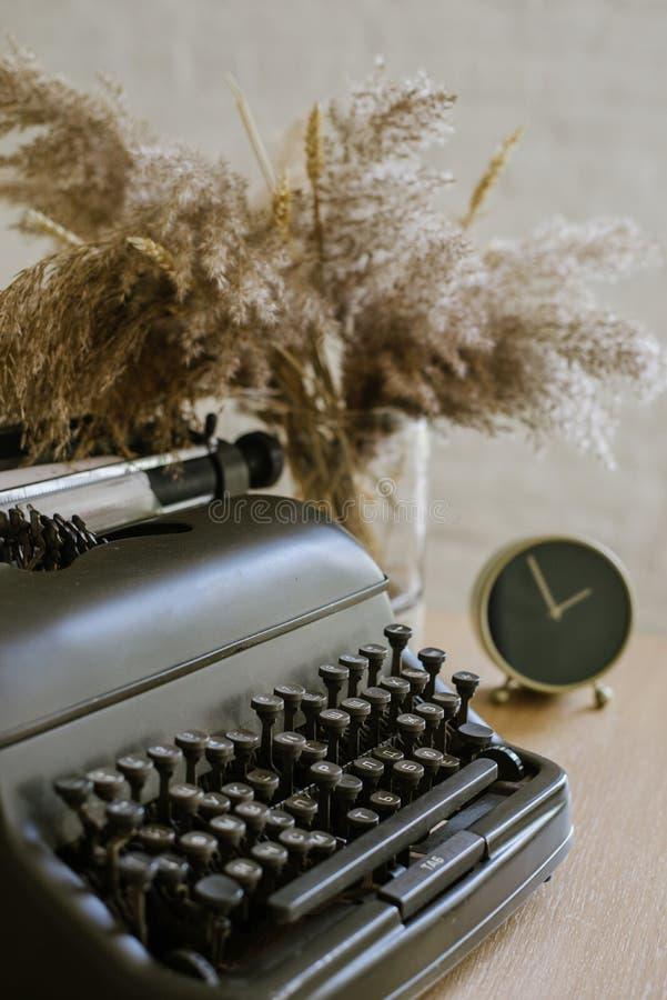 Παλαιά γραφομηχανή σε ένα ξύλινο επιτραπέζιο υπόβαθρο με τα έγγραφα έτοιμα για ένα καινούργιο βιβλίο ή ένα μυθιστόρημα με πολλές  στοκ εικόνα με δικαίωμα ελεύθερης χρήσης
