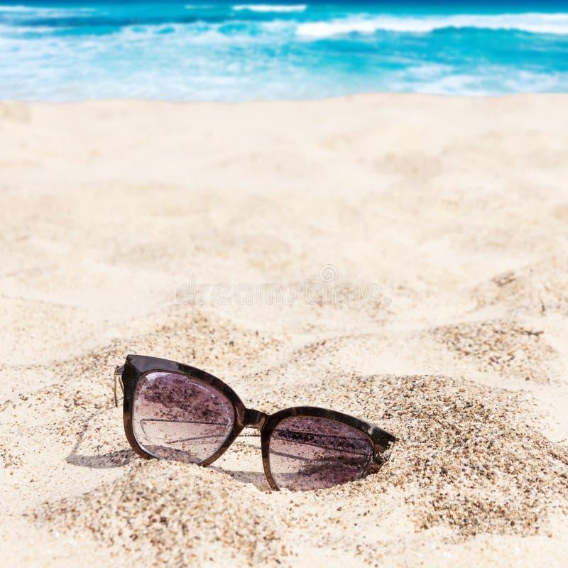 Παλαιά εγκαταλειμμένα γυαλιά ηλίου στην άμμο παραλιών με τον τυρκουάζ ωκεανό στο υπόβαθρο στοκ φωτογραφία με δικαίωμα ελεύθερης χρήσης