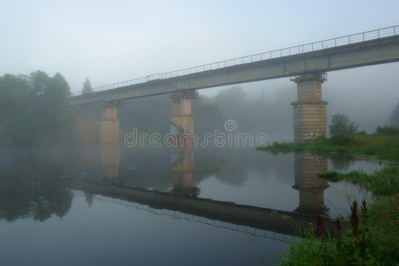 Παλαιά εγκαταλειμμένη γέφυρα πέρα από τον ποταμό μισό-που καλύπτεται με την υδρονέφωση predawn στοκ εικόνες
