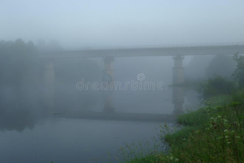 Παλαιά εγκαταλειμμένη γέφυρα πέρα από τον ποταμό μισό-που καλύπτεται με την υδρονέφωση predawn στοκ εικόνα
