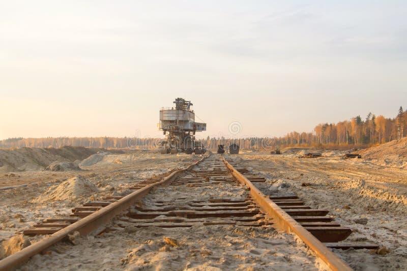 Παλαιά εγκαταλειμμένη διαδρομή σιδηροδρόμων Σκουριασμένος δεσμός σιδηροδρόμου Γιγαντιαίος στοιβαχτής Εκσκαφέας αλυσίδων κάδων σε  στοκ εικόνες