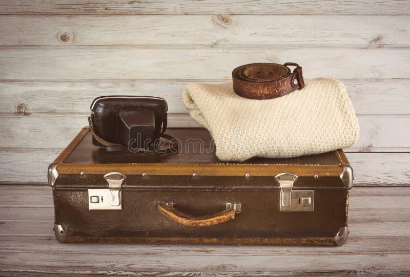 Παλαιά εκλεκτής ποιότητας βαλίτσα στο δωμάτιο στον ξύλινο ελαφρύ πίνακα στοκ φωτογραφία