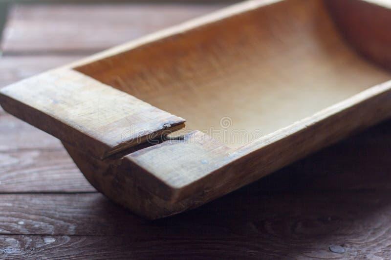 Παλαιά εργαλεία κουζινών, παλαιά ξύλινη γούρνα με τη ρωγμή στο ξύλινο υπόβαθρο στοκ φωτογραφίες με δικαίωμα ελεύθερης χρήσης
