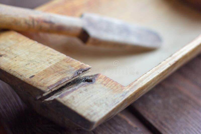Παλαιά εργαλεία κουζινών, παλαιά ξύλινη γούρνα με τη ρωγμή στο ξύλινο υπόβαθρο στοκ εικόνα με δικαίωμα ελεύθερης χρήσης