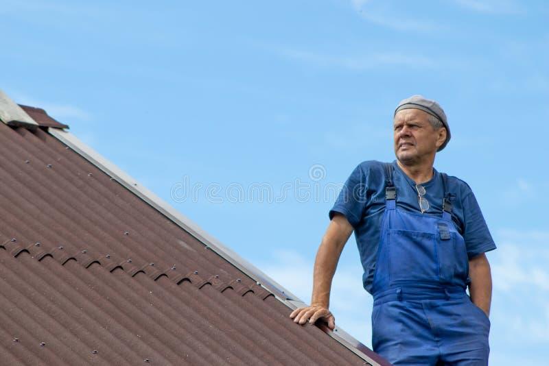 Παλαιά εργασία ατόμων, που στηρίζεται μια στέγη ενός σπιτιού χωρίς οποιεσδήποτε συσκευές ασφάλειας, που φορά τα ενδύματα εργασίας στοκ φωτογραφίες