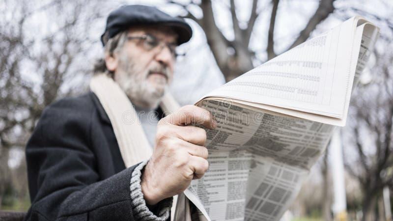 Παλαιά εφημερίδα ανάγνωσης ατόμων στο πάρκο στοκ εικόνα
