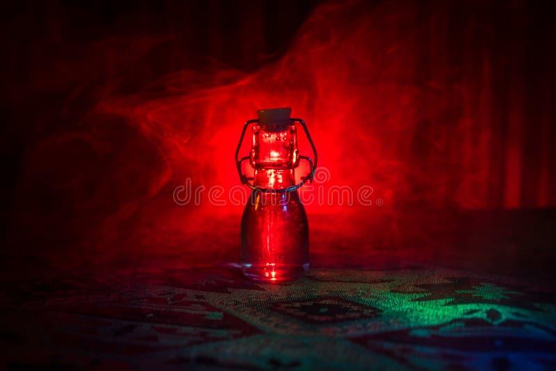 Παλαιά και εκλεκτής ποιότητας μπουκάλια γυαλιού στο σκοτεινό ομιχλώδες υπόβαθρο με το φως Δηλητήριο ή μαγική υγρή έννοια στοκ φωτογραφίες