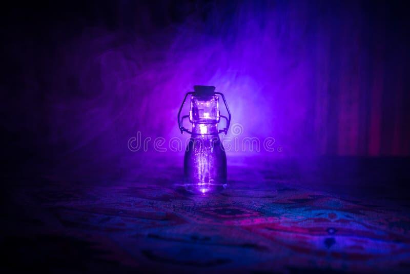 Παλαιά και εκλεκτής ποιότητας μπουκάλια γυαλιού στο σκοτεινό ομιχλώδες υπόβαθρο με το φως Δηλητήριο ή μαγική υγρή έννοια στοκ φωτογραφία