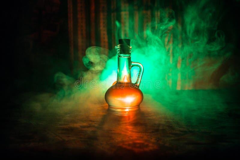 Παλαιά και εκλεκτής ποιότητας μπουκάλια γυαλιού στο σκοτεινό ομιχλώδες υπόβαθρο με το φως Δηλητήριο ή μαγική υγρή έννοια στοκ εικόνα με δικαίωμα ελεύθερης χρήσης