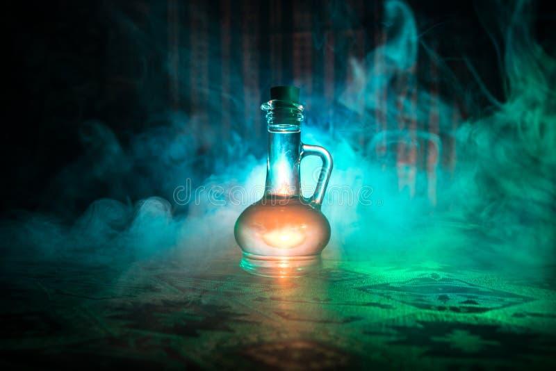 Παλαιά και εκλεκτής ποιότητας μπουκάλια γυαλιού στο σκοτεινό ομιχλώδες υπόβαθρο με το φως Δηλητήριο ή μαγική υγρή έννοια στοκ φωτογραφία με δικαίωμα ελεύθερης χρήσης