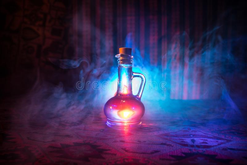 Παλαιά και εκλεκτής ποιότητας μπουκάλια γυαλιού στο σκοτεινό ομιχλώδες υπόβαθρο με το φως Δηλητήριο ή μαγική υγρή έννοια στοκ φωτογραφίες με δικαίωμα ελεύθερης χρήσης