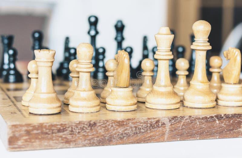 Παλαιά καλά χρησιμοποιημένα ξύλινα κομμάτια σκακιού σε μια σκακιέρα, αναδρομική έννοια ηγεσίας στο άσπρο υπόβαθρο στοκ εικόνες με δικαίωμα ελεύθερης χρήσης