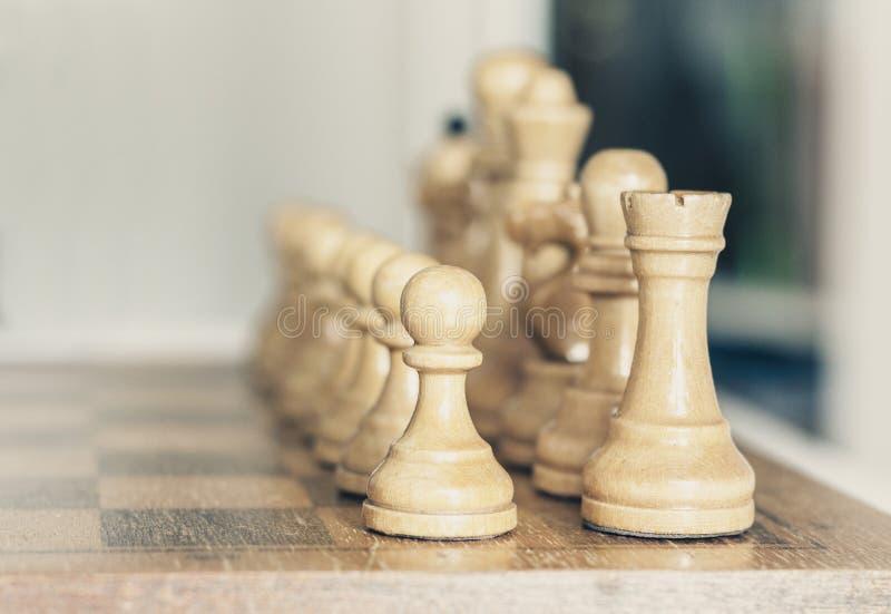 Παλαιά καλά χρησιμοποιημένα ξύλινα κομμάτια σκακιού σε μια σκακιέρα, αναδρομική έννοια ηγεσίας στο άσπρο υπόβαθρο στοκ εικόνες