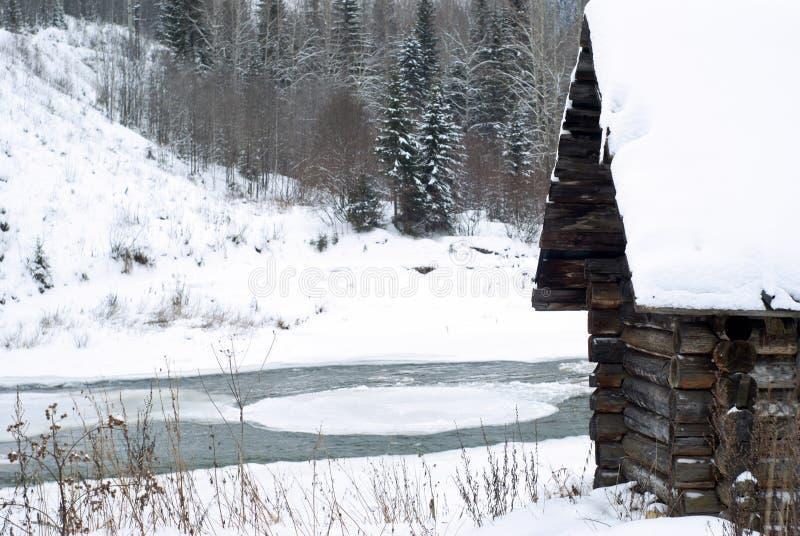 Παλαιά καλύβα κούτσουρων στην όχθη ποταμού στο χειμερινό τοπίο στοκ εικόνες με δικαίωμα ελεύθερης χρήσης