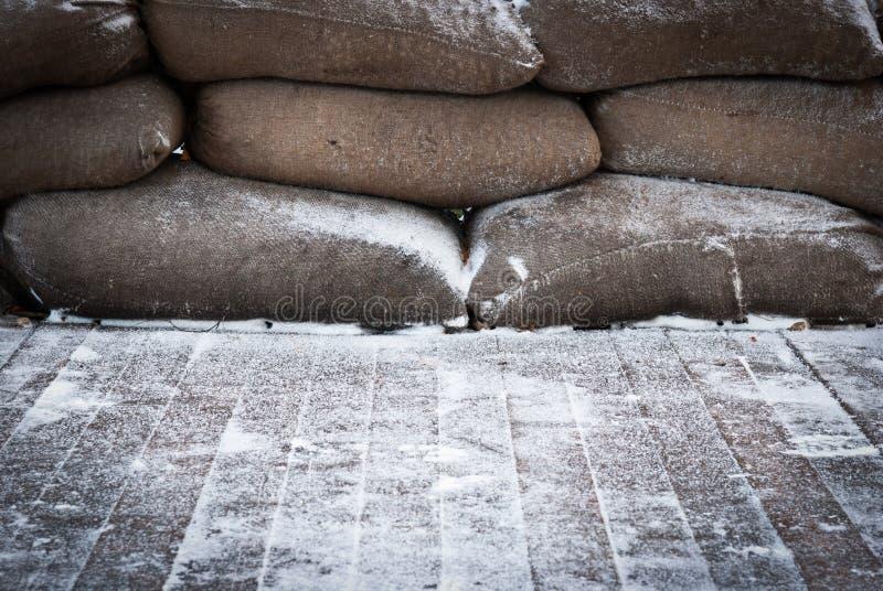 Παλαιά καφετιά sandbags στο χιονισμένο ξύλινο πάτωμα στοκ φωτογραφία με δικαίωμα ελεύθερης χρήσης