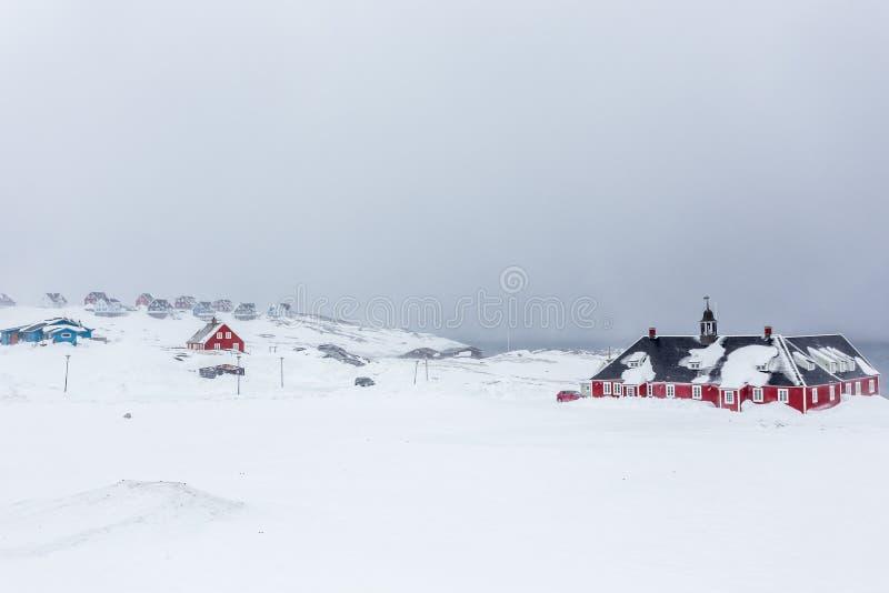 Παλαιά κόκκινα σπίτια κτηρίου και Inuit στο υπόβαθρο μεταξύ sn στοκ φωτογραφίες με δικαίωμα ελεύθερης χρήσης