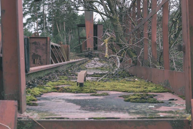 παλαιά κόκκινη γέφυρα μετάλλων πέρα από το νερό - εκλεκτής ποιότητας αναδρομικός κοιτάζει στοκ εικόνα