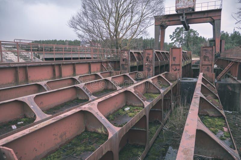 παλαιά κόκκινη γέφυρα μετάλλων πέρα από το νερό - εκλεκτής ποιότητας αναδρομικός κοιτάζει στοκ εικόνες