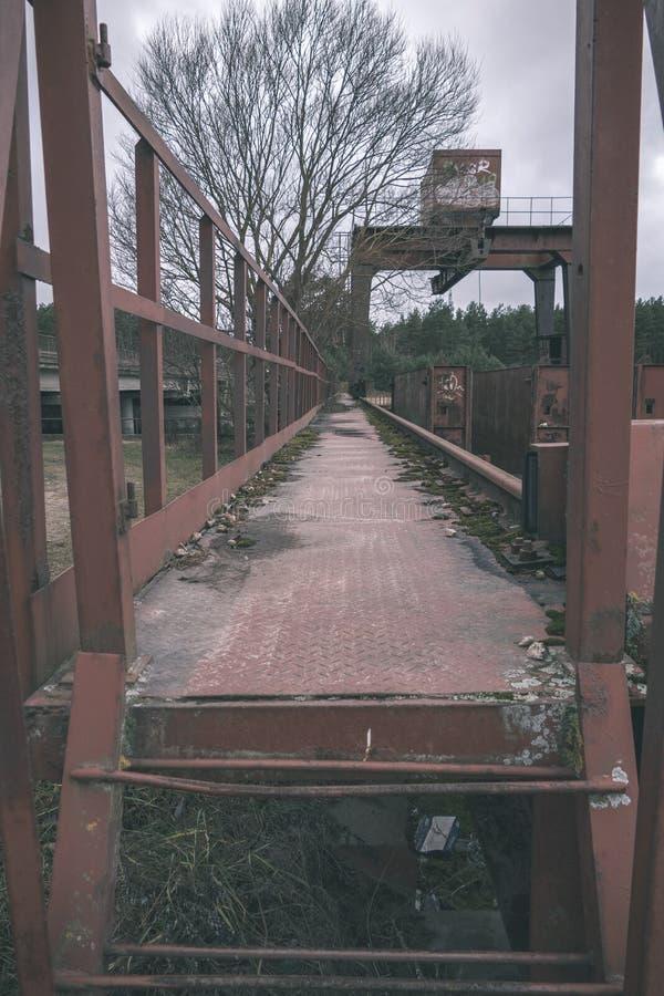 παλαιά κόκκινη γέφυρα μετάλλων πέρα από το νερό - εκλεκτής ποιότητας αναδρομικός κοιτάζει στοκ φωτογραφίες