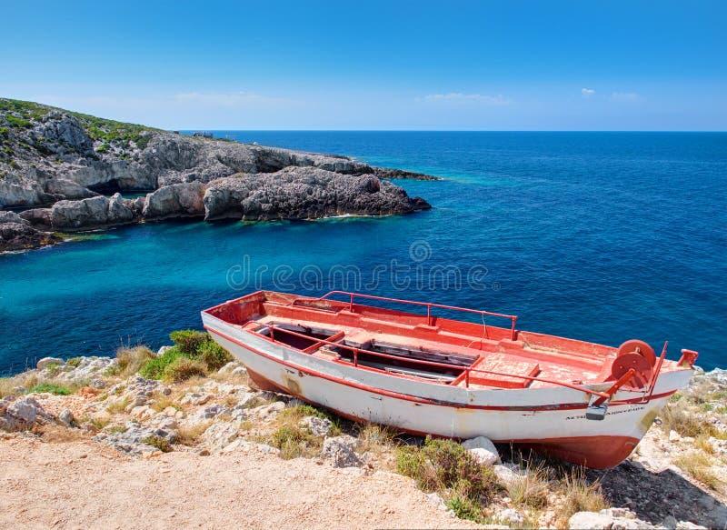 Παλαιά κόκκινη και άσπρη πολύ παλαιά βάρκα και όμορφη άποψη σχετικά με το μπλε νερό της ιόνιας θάλασσας στο νησί Ζάκυνθος στην Ελ στοκ εικόνα με δικαίωμα ελεύθερης χρήσης
