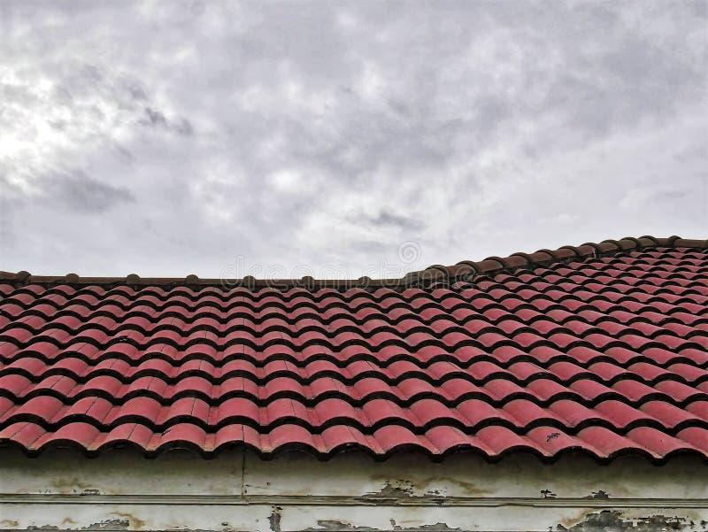 Παλαιά κόκκινη κεραμωμένη στέγη ενάντια στο νεφελώδη ουρανό στοκ εικόνες