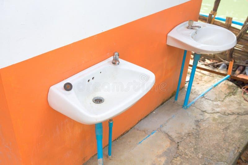 Παλαιά λεκάνη πλυσίματος με την παλαιά στρόφιγγα με τον μπλε σωλήνα pve στοκ εικόνες με δικαίωμα ελεύθερης χρήσης