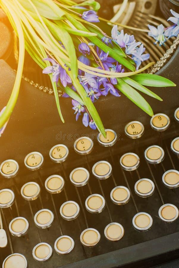 Παλαιά μαύρη εκλεκτής ποιότητας γραφομηχανή με τα μπλε ρομαντικά λουλούδια άνοιξη στοκ φωτογραφία με δικαίωμα ελεύθερης χρήσης