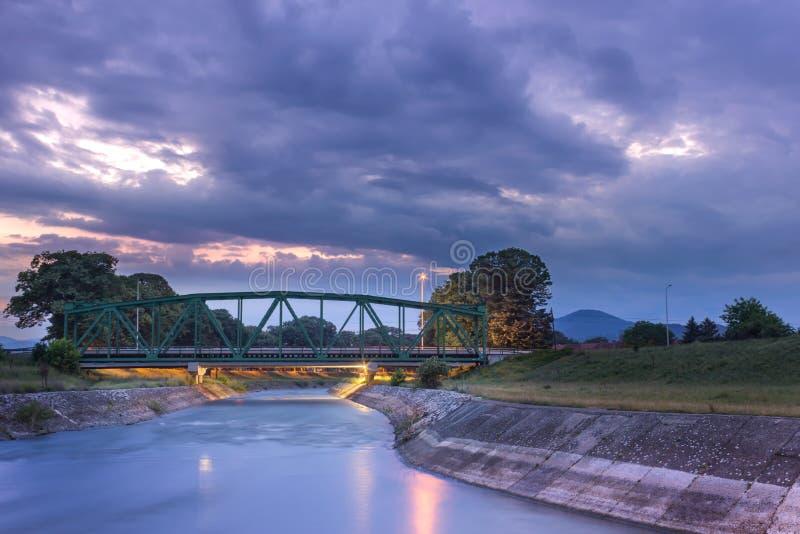Παλαιά, μεταλλική γέφυρα σιδηροδρόμου και αντανακλάσεις ποταμών κατά τη διάρκεια του δραματικού ηλιοβασιλέματος στοκ φωτογραφίες με δικαίωμα ελεύθερης χρήσης