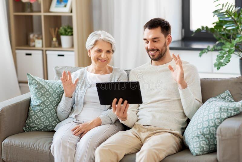 Παλαιά μητέρα και ενήλικος γιος με το PC ταμπλετών στο σπίτι στοκ φωτογραφία με δικαίωμα ελεύθερης χρήσης