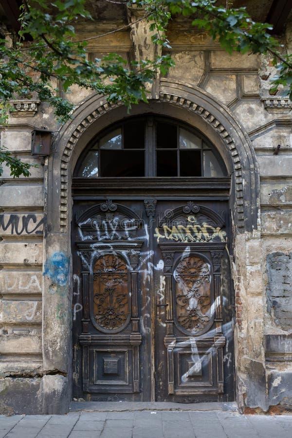 Παλαιά μοντέρνη ξύλινη πόρτα με τη βρώμικη πρόσοψη στοκ εικόνες με δικαίωμα ελεύθερης χρήσης