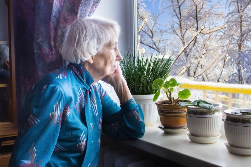 Παλαιά μόνη συνεδρίαση γυναικών κοντά στο παράθυρο στο σπίτι του στοκ φωτογραφίες με δικαίωμα ελεύθερης χρήσης