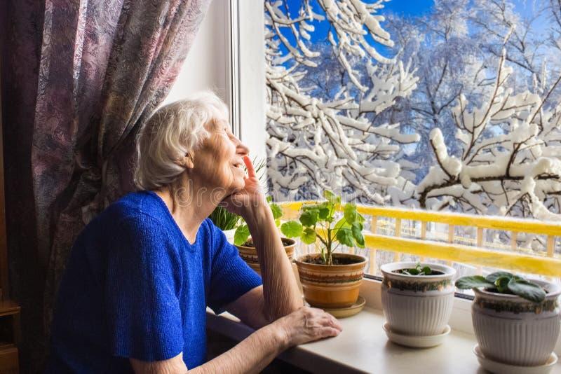 Παλαιά μόνη συνεδρίαση γυναικών κοντά στο παράθυρο στο σπίτι του στοκ εικόνες