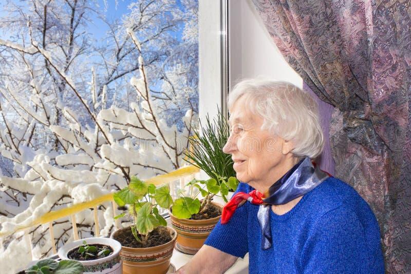 Παλαιά μόνη συνεδρίαση γυναικών κοντά στο παράθυρο στο σπίτι του στοκ φωτογραφία με δικαίωμα ελεύθερης χρήσης