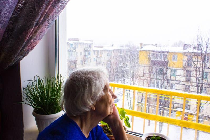 Παλαιά μόνη συνεδρίαση γυναικών κοντά στο παράθυρο στο σπίτι του στοκ εικόνα