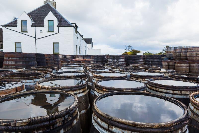 Παλαιά ξύλινα βαρέλια και βαρέλια με την ενιαία βύνη σκωτσέζικη στην οινοπνευματοποιία ουίσκυ στη Σκωτία στοκ φωτογραφία με δικαίωμα ελεύθερης χρήσης