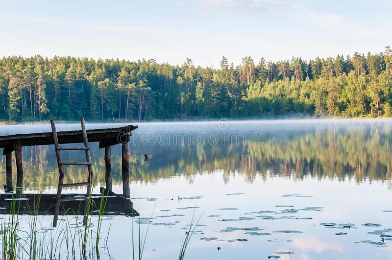 Παλαιά ξύλινη αποβάθρα με τη σκάλα στην ακόμα ομιχλώδη λίμνη με το δάσος στο υπόβαθρο στην ανατολή στοκ φωτογραφία