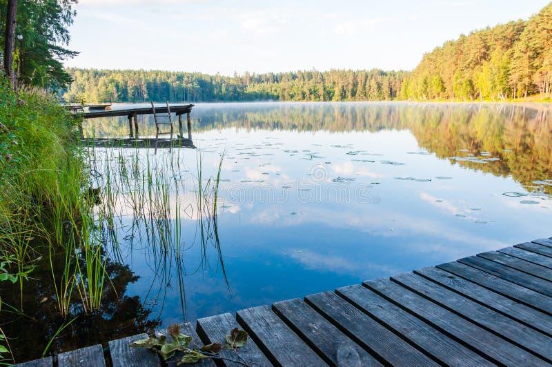 Παλαιά ξύλινη αποβάθρα με τη σκάλα στην ακόμα ομιχλώδη λίμνη με το δάσος στο υπόβαθρο στην ανατολή στοκ φωτογραφίες με δικαίωμα ελεύθερης χρήσης