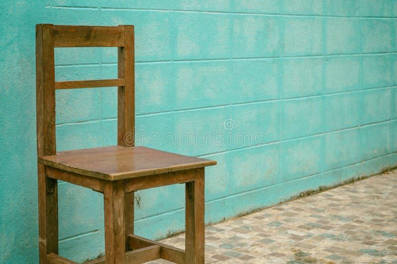 Παλαιά ξύλινη καρέκλα στο μπλε υπόβαθρο τοίχων στοκ εικόνα