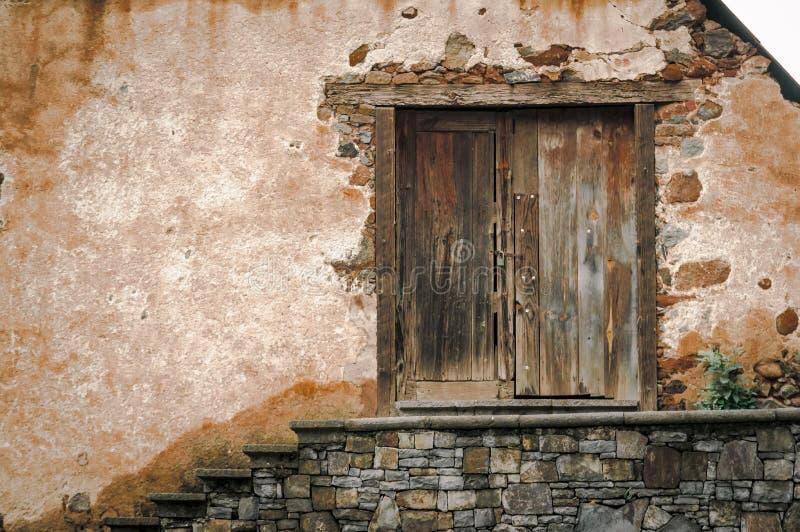 Παλαιά ξύλινη πόρτα ενός αγροκτήματος με τον τοίχο βράχου και τα σκαλοπάτια βράχων στοκ φωτογραφίες