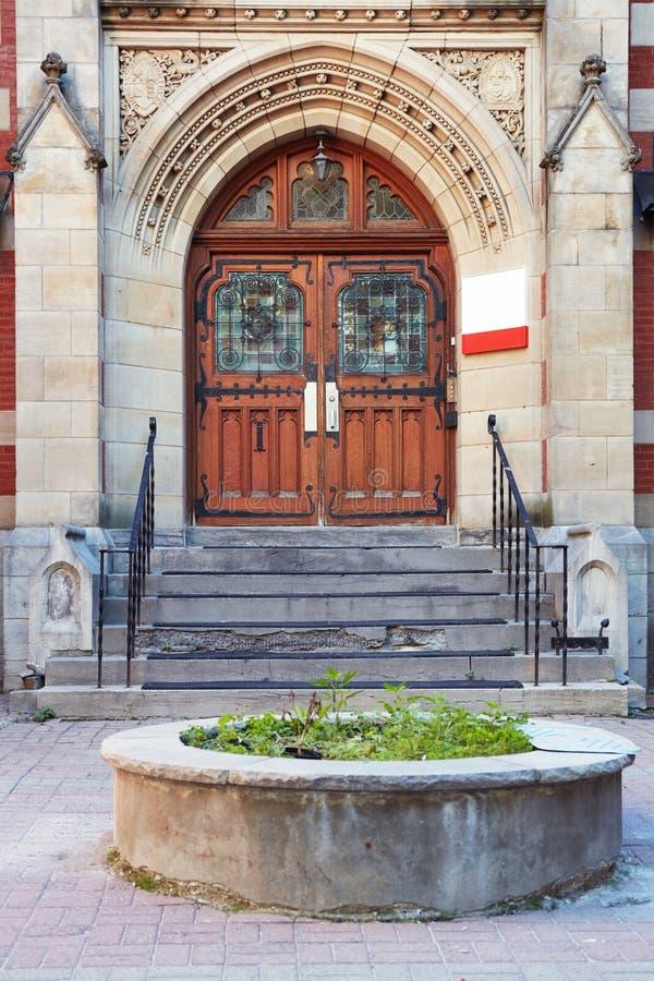 Παλαιά ξύλινη πόρτα με τα παράθυρα, τη χαρασμένα αψίδα πετρών και τα βήματα της εισόδου ενός ιστορικού κτηρίου στο Μόντρεαλ, Κεμπ στοκ εικόνες