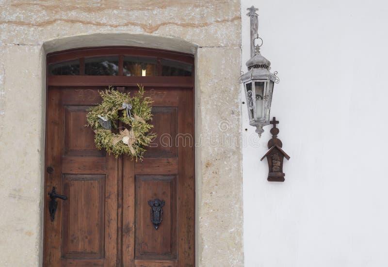Παλαιά ξύλινη πόρτα με την επένδυση, το στεφάνι, το φανάρι και το σταυρό ψαμμίτη στοκ φωτογραφίες με δικαίωμα ελεύθερης χρήσης