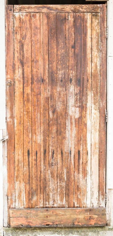 Παλαιά ξύλινη πόρτα με την κίτρινη αποφλοίωση χρωμάτων μακριά στοκ εικόνες με δικαίωμα ελεύθερης χρήσης