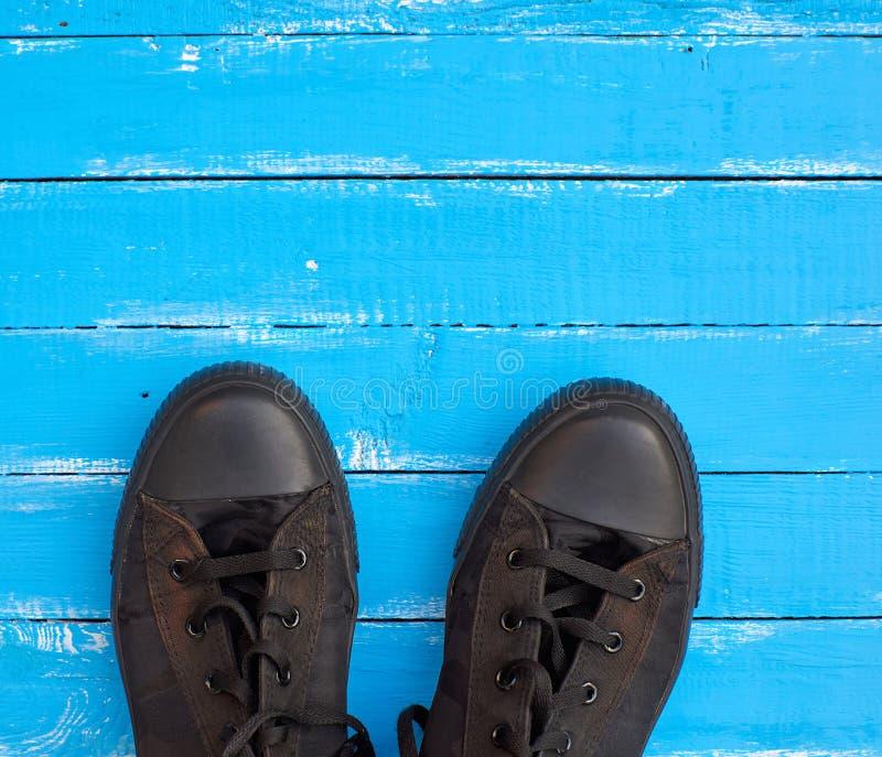 παλαιά πάνινα παπούτσια ατόμων σε μια μπλε ξύλινη επιφάνεια στοκ εικόνες